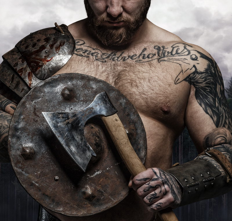 tattooed male's body with vikings shield and axe.
